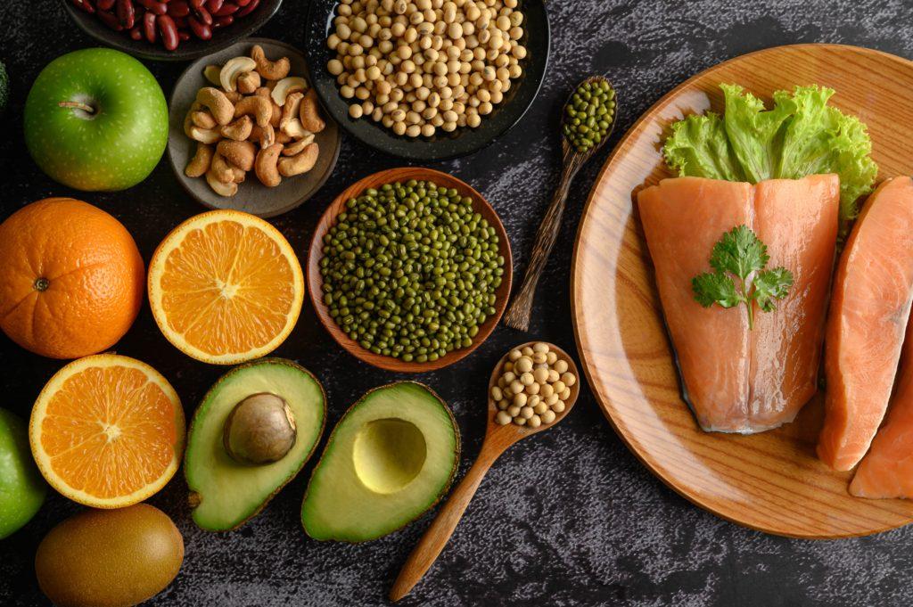 Legumes frutas grãos e pedaços de salmão sobre placa de mármore