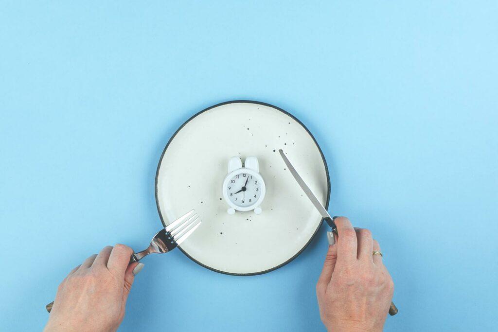 Mão segurando talheres sobre um prato com um relógio no centro