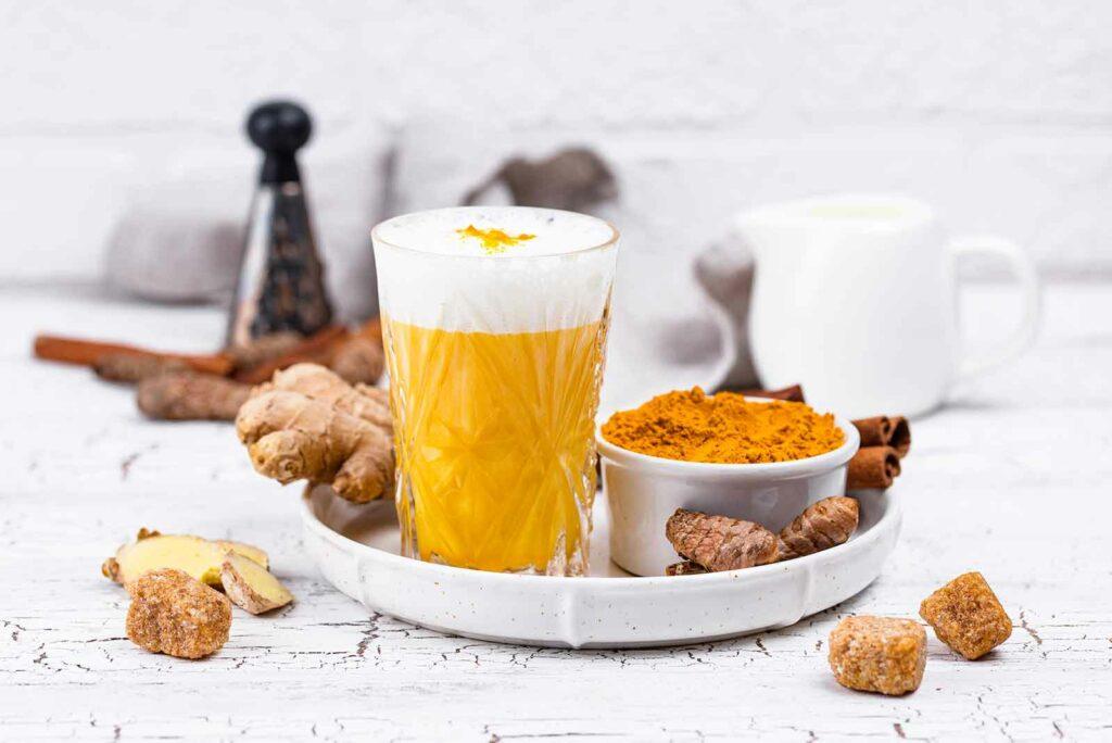 Copo de golden milk numa bandeja cercado de seus igredientes