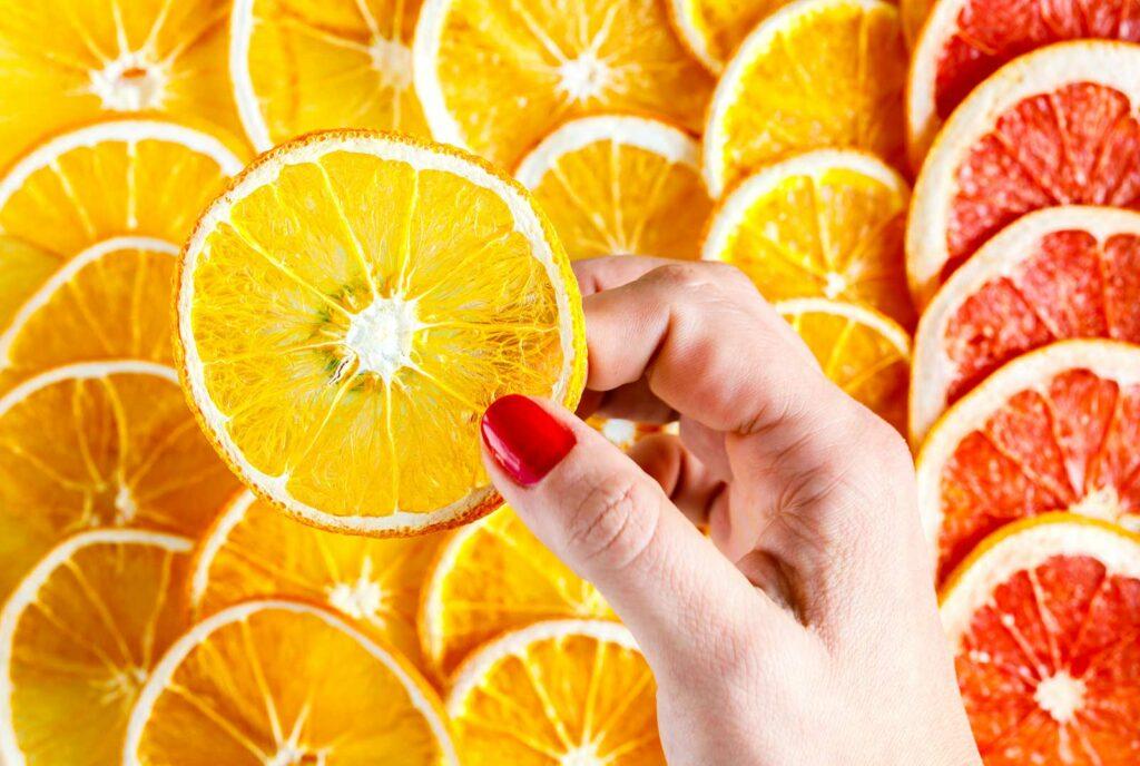 mão segurando uma fatia de laranja, alimento que reforça a imunidade