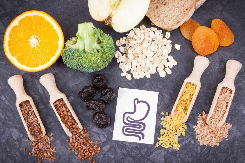 alimentos que ajudam na flora intestinal em cima de uma mesa, grãos, verduras, frutas secas